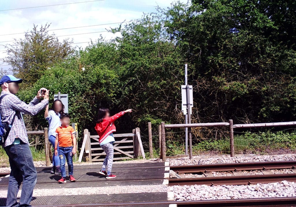 Family taking photos on a level crossing.